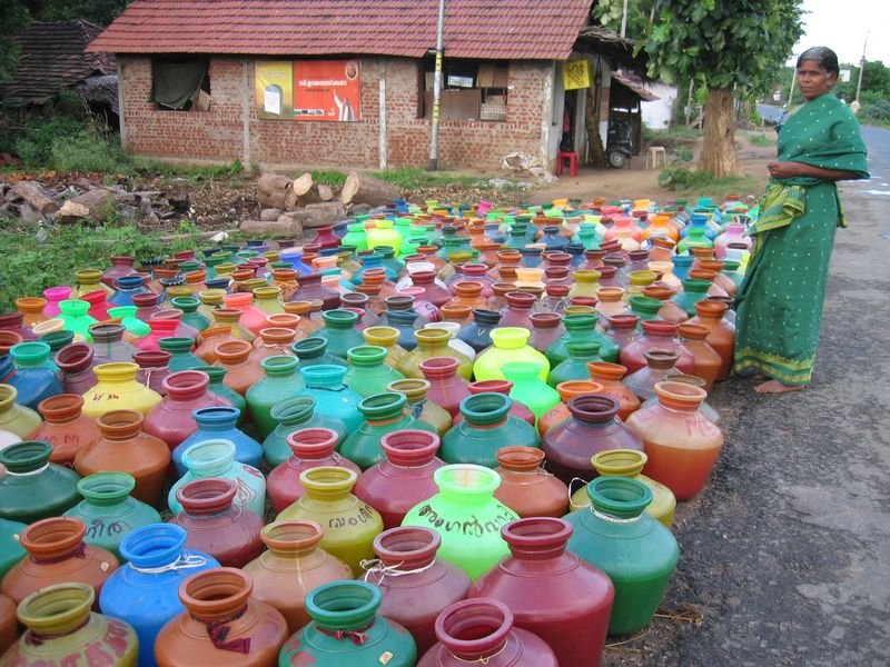 Mylamma with plastic pitchers in the foreground